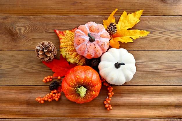 Herbst, herbstkomposition mit bunten blättern, tannenzapfen und kürbissen auf holzhintergrund, kopierraum.