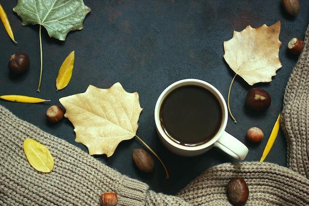 Herbst, herbstlaub, heißer dampfender kaffee und ein warmer schal oder eine strickjacke. saison-, morgenkaffee, sonntag entspannend und stilllebenkonzept.