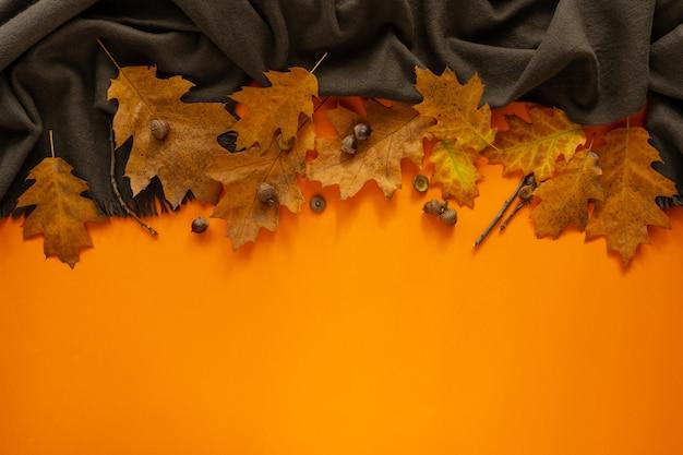 Herbst. herbstrahmen aus gefallenen blättern auf einem leuchtend orangefarbenen hintergrund. banner.