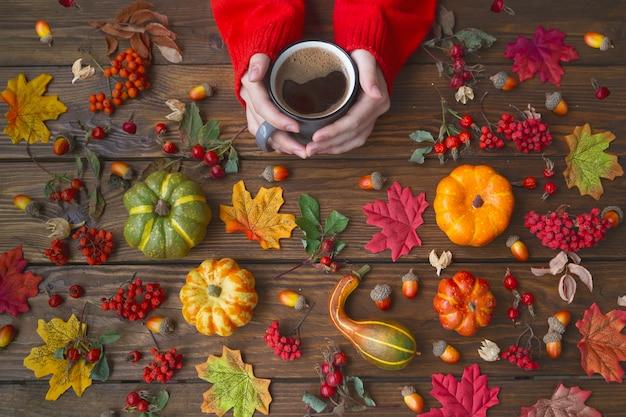 Herbst hintergrund. die hände eines mädchens in einem roten pullover halten eine tasse kaffee auf einem holztisch mit kürbissen, blättern, eicheln und beeren.