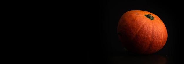 Herbst-hokkaido-kürbis auf einem schwarzen fahnenhintergrund mit kopienraum. frischgemüse-lebensmittelkonzeptfoto