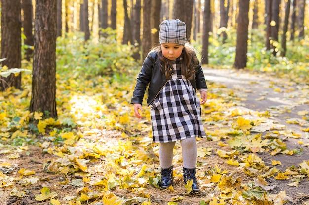 Herbst, kindheit, menschenkonzept - kleines glückliches mädchen, das im herbstpark spaziert.