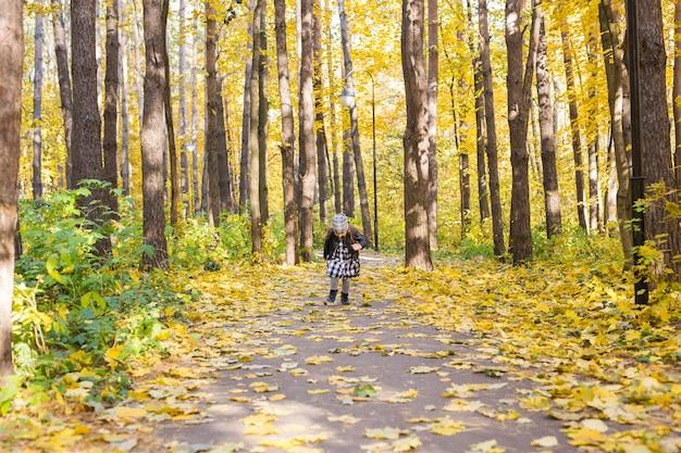 Herbst-, kindheits- und saisonkonzept - kleines mädchen, das im herbstpark spielt
