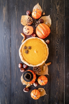 Herbst-konzept. hausgemachter kürbiskuchen mit herbstlaub auf rustikalem hintergrund
