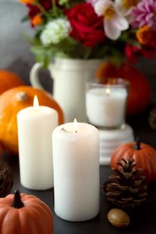Herbst kreativer hintergrund mit kerzen, herbstblumen, tannenzapfen und kürbissen. dunkler stimmungsvoller und gemütlicher herbst