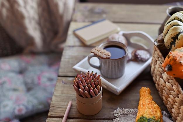 Herbst, kürbise, heißer dampfender tasse kaffee auf einem holztisch. saisonale, morgenkaffee, sonntag entspannend und stillleben. pläne für den tag