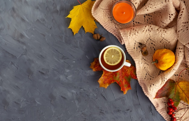 Herbst-layout. gefallene helle blätter, aromakerze, zapfen, kürbis und tasse heißen tee mit zitrone auf einem hölzernen hintergrund. ansicht von oben