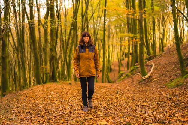 Herbst lebensstil, eine junge frau in einer gelben jacke in einem wald voller bäume. artikutza wald in san sebastin, gipuzkoa, baskenland. spanien