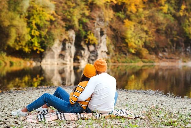 Herbst lifestyle, mode, familie. glückliches stilvolles modepaar, das schöne landschaft am herbsttag genießt. herbstmode. junge familie auf einem spaziergang auf der natur