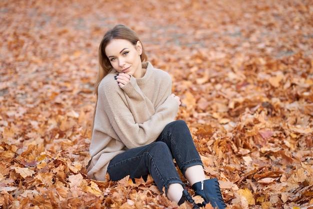 Herbst look für jeden tag. schönes stilvolles blondes selbstbewusstes mädchen, das pullover, schwarze jeans und schwarze lederstiefel trägt, die im herbstpark sitzen.