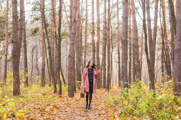 Herbst, mode, menschen konzept - frau mit braunem retro-koffer, der durch den herbstpark geht