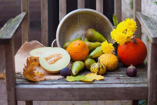 Herbst natur. herbstfrüchte auf holz. das erntedankfest. herbstgemüse auf einem alten stuhl im garten, freier platz für text, gelbe blumen