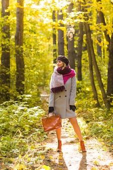 Herbst, natur, menschen konzept - schöne junge frau in einem grauen mantel und einer baskenmütze stehend