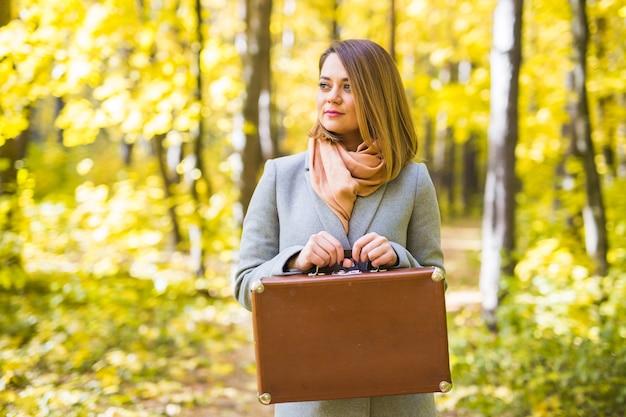 Herbst, natur und menschen konzept - porträt der schönen lächelnden frau mit braunem koffer in