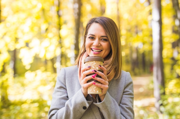 Herbst-, natur- und personenkonzept - junge schöne frau im blauen mantel, der eine tasse kaffee hält