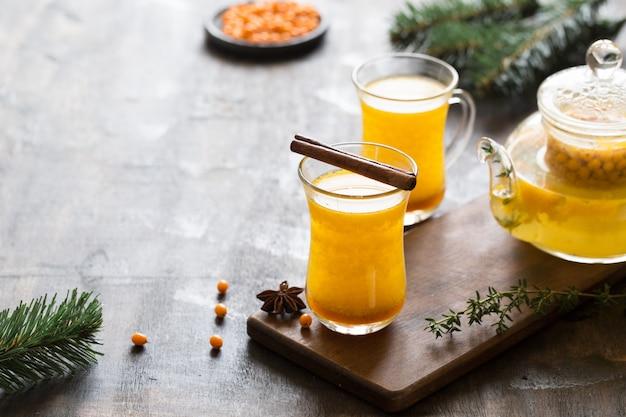 Herbst- oder winter-sanddorngetränk. sanddorntee, selektiver fokus. stillleben, essen und trinken, saisonal und an feiertagen