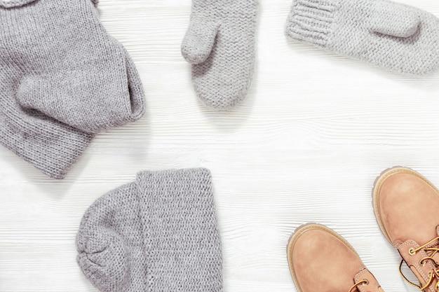 Herbst oder winter weibliches outfit. set von kleidung und schuhen. warme strickmütze, fäustlinge und grau gefärbte stiefel in lederorange. sicht von oben.