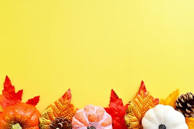 Herbst orange blätter, fallen abstrakten rahmen mit bunten blättern, tannenzapfen und kürbissen auf hellem hintergrund, kopienraum.