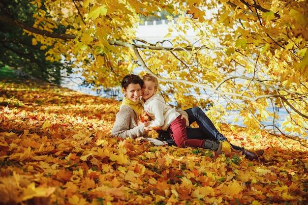 Herbst park. mutter und kind spielen zusammen. glückliche liebevolle familie, die spaß hat. modefamilienkonzept - stilvolle mutter- und kinderkleidung.