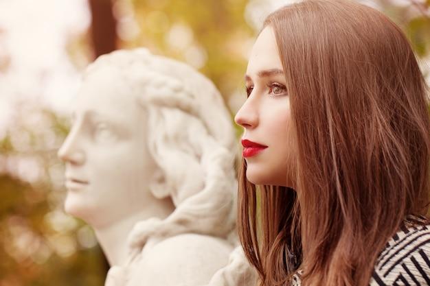 Herbst-porträt der hübschen frau und der marmorstatue im freien. profil
