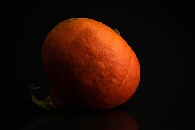 Herbst red kuri oder orange kürbis auf schwarzem hintergrund. frischgemüse-lebensmittelkonzeptfoto