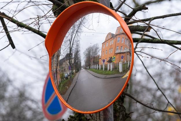 Herbst. reflexion einer stadtstraße in einem konvexen außenspiegel.