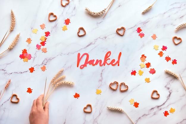 Herbst saisonaler hintergrund mit weizenähren und papierkonfetti. papiertext danke bedeutet danke in deutscher sprache. flach lag auf weißem marmortisch.