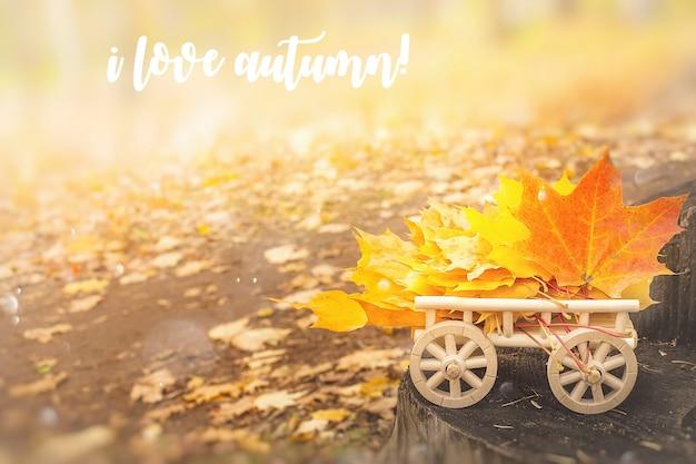 Herbst-schriftzug-karte. ahornblätter auf einem hölzernen wagen.