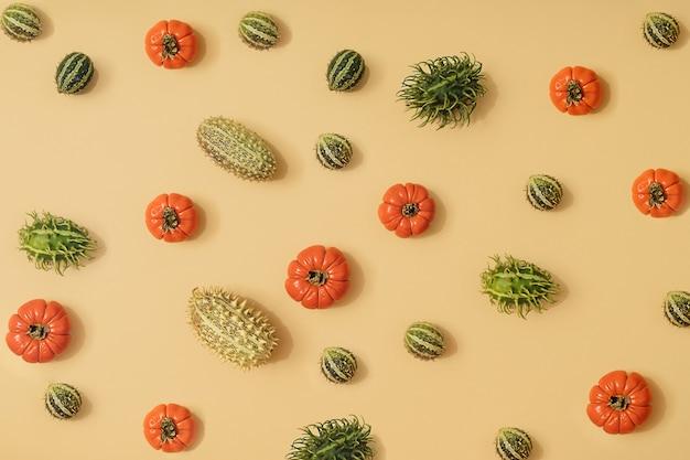 Herbst sonnenbeschienener gelber hintergrund mit kürbissen, physalis, tomaten und grünen früchten der saison. flache ernte oder halloween-konzept. kreatives layout von buntem gemüse. platz kopieren.