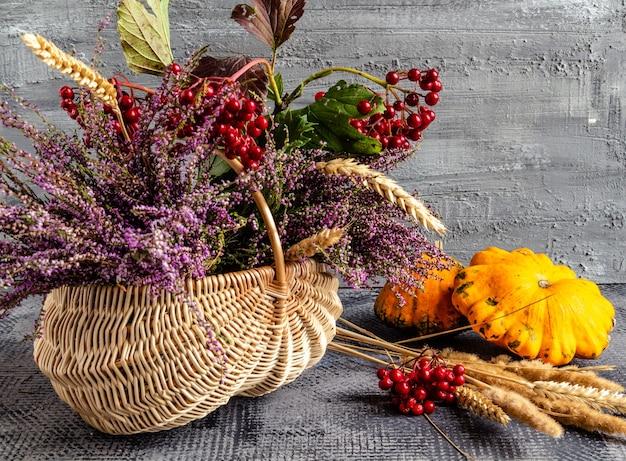Herbst-stillleben-korb mit heidekraut und viburnum und früchten zum erntedankfest
