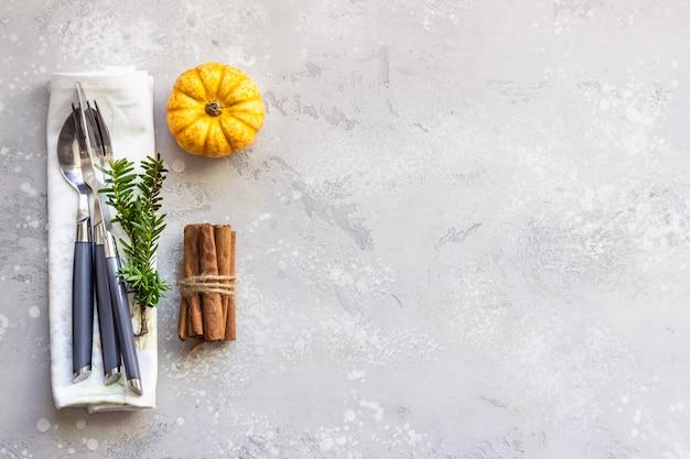 Herbst tabelleneinstellung. mini dekorative kürbis, gabel, messer, löffel und zimtstangen.