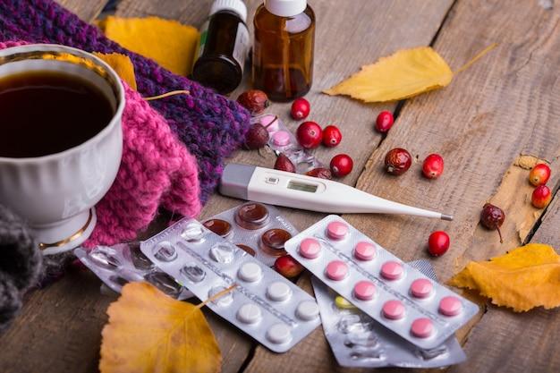 Herbst und gesundheitsvorsorge. hausapotheke - tasse tee, pillen und thermometer auf holzhintergrund