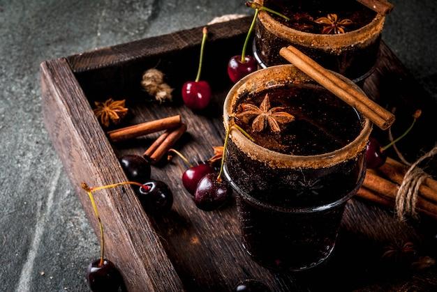 Herbst- und wintergetränke. heiße kirschsangria mit zimt, anis, wein und gewürzen. auf einem dunklen stein und holz mit zutaten, in tablett