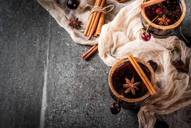 Herbst- und wintergetränke. heiße kirschsangria mit zimt, anis, wein und gewürzen. auf einem dunklen und hölzernen stein mit bestandteilen, draufsicht
