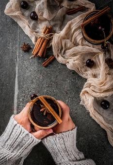 Herbst- und wintergetränke. heiße kirschsangria mit zimt, anis, wein und gewürzen. auf einem stein dunkel und aus holz. mädchen halten glas mit getränk. frauenhänden in pullover. ansicht von oben