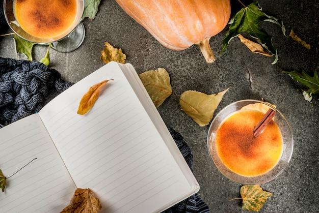 Herbst- und wintergetränke. thanksgiving- und halloween-cocktails. kürbiskuchen margarita mit zimtstange, auf schwarzer steintabelle. gemütliches zuhause, mit herbstlaub, plaid, kürbis, buch, draufsicht
