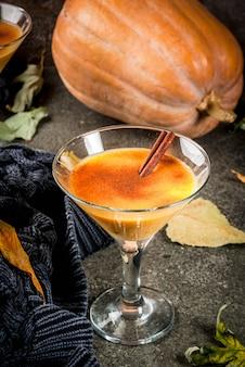 Herbst- und wintergetränke. thanksgiving- und halloween-cocktails. kürbiskuchen margarita mit zimtstange, auf schwarzer steintabelle. gemütliches zuhause, mit herbstlaub, plaid, kürbis, kopienraum