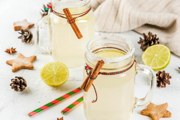 Herbst- und wintergetränke. weihnachtsfeiertagsgetränk. festliches schneeballcocktail mit limettensaft, zimt, likör, zucker und anissternen. auf weißer tabelle mit weihnachtsdekoration copyspace