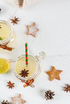 Herbst- und wintergetränke. weihnachtsfeiertagsgetränk. festliches schneeballcocktail mit limettensaft, zimt, likör, zucker und anissternen. auf weißer tabelle mit weihnachtsdekoration draufsicht