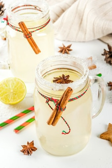 Herbst- und wintergetränke. weihnachtsfeiertagsgetränk. festliches schneeballcocktail mit limettensaft, zimt, likör, zucker und anissternen. auf weißer tabelle mit weihnachtsdekoration