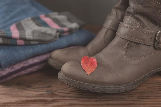 Herbst weibliches outfit. satz kleidung, schuhe und roturlaub auf hölzernem hintergrund