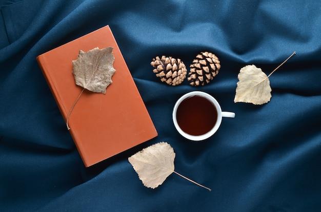 Herbst winter atmosphäre. eine tasse tee, trockene blätter, tannenzapfen auf dem dunklen bettlaken. draufsicht. flach liegen.