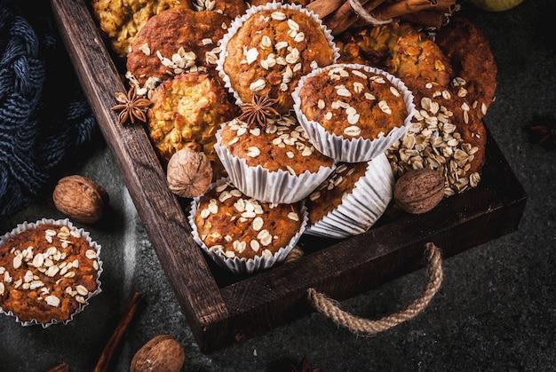 Herbst winter gebäck. veganes essen. gesunde hausgemachte kekse, muffins mit nüssen, äpfeln, haferflocken. gemütliche atmosphäre, warme decke, zutaten. dunkler steintisch.