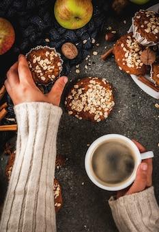 Herbst winter gebäck. veganes essen. gesunde kekse, muffins mit nüssen, äpfeln, haferflocken. gemütliche atmosphäre, warme decke, mädchen trinken kaffee, hände im bild. dunkler steintisch. ansicht von oben