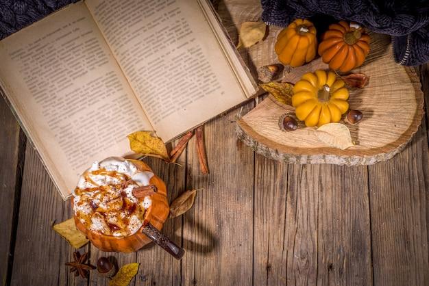 Herbst, wintergetränk für weihnachten, thanksgiving, halloween. lustige tasse würziger kürbislatte, heiße schokolade, mit schlagsahne, marshmallow, gewürzen mit buch, warmem plaid und dekoration