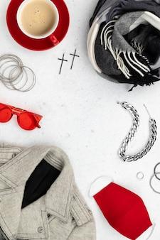 Herbst winterkleidung der frauen schauen mit schutzmaske auf grauem tisch. flache lay draufsicht neue normale modekomposition.