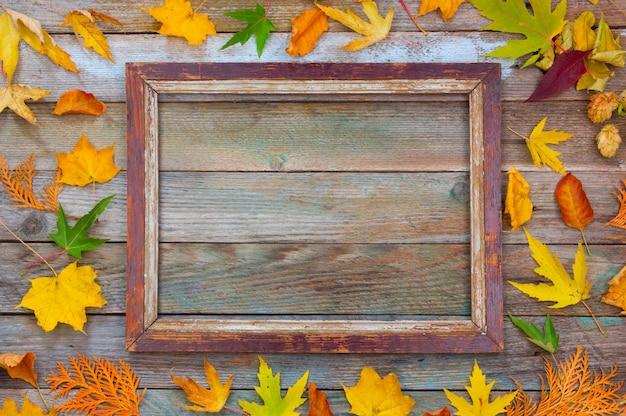 Herbst zusammensetzung. heller herbstlaub und bilderrahmen auf einem hölzernen hintergrund