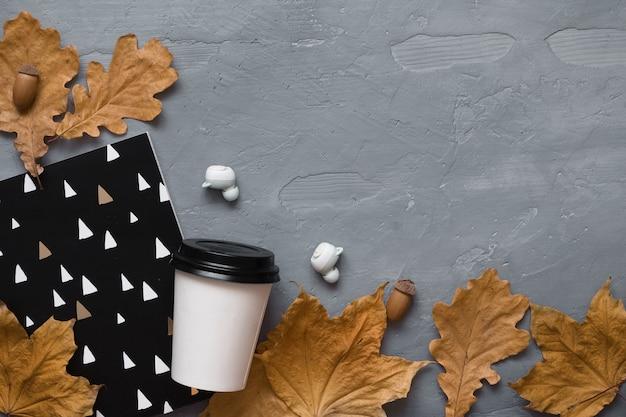 Herbst zusammensetzung. kaffee zum mitnehmen, notebook, kopfhörer mit herbstlaub. flache lage, draufsicht, kopienraum.