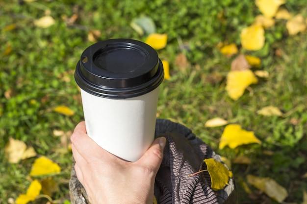 Herbst zusammensetzung. weibliche hand, die einen tasse kaffee hält. kaffee zum mitnehmen im herbstlaub. herbst picknick consept.