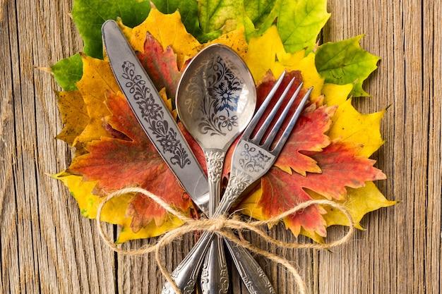 Herbstabendessengedeck für erntedankfest mit bunten ahornblättern auf rustikalen hölzernen brettern